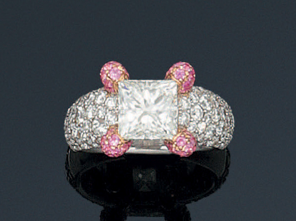 Bague en or gris ornée d'un diamant princesse bordé de pavages de diamants taillés…