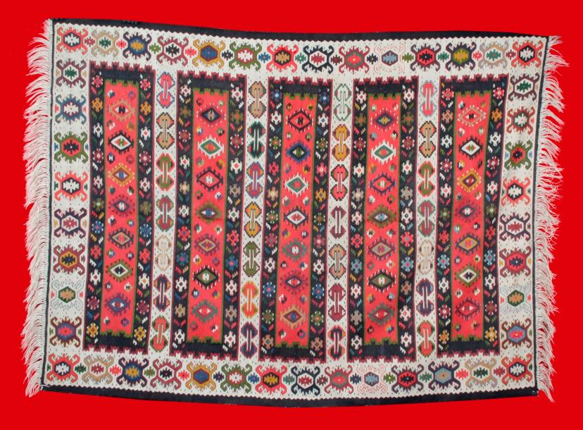 GRAND TAPIS KILIM ROUMAIN vers 1960. A décor de bandes et originale bordure à décor…