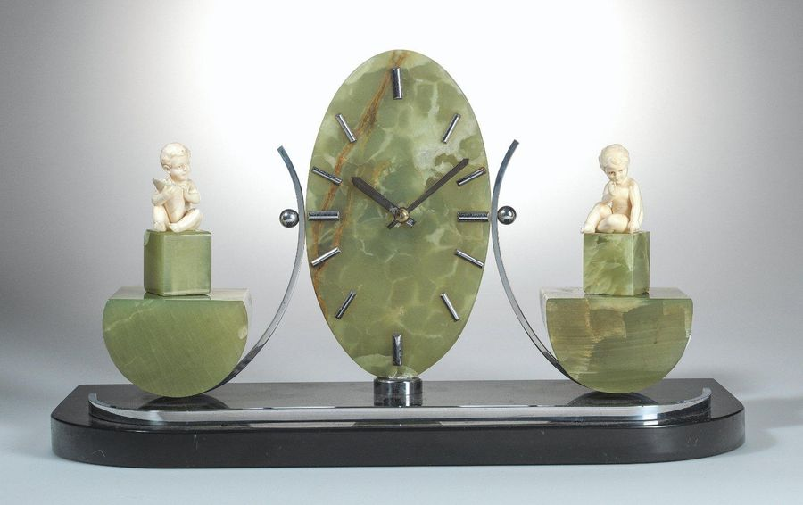 An Art Deco table clock or mantel clock two seated children on either side by Fe…
