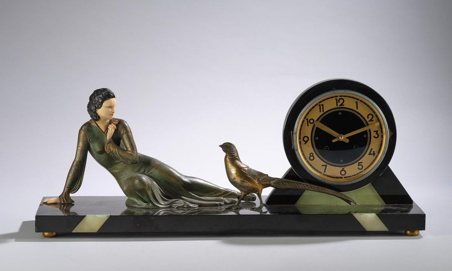 E. Menneville, an Art Deco mantel clock with a recumbent female figure with a ro…