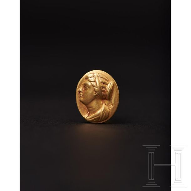 A Ptolemaic gold ring with the portrait of Berenice II, 3rd century B.C. A solid…