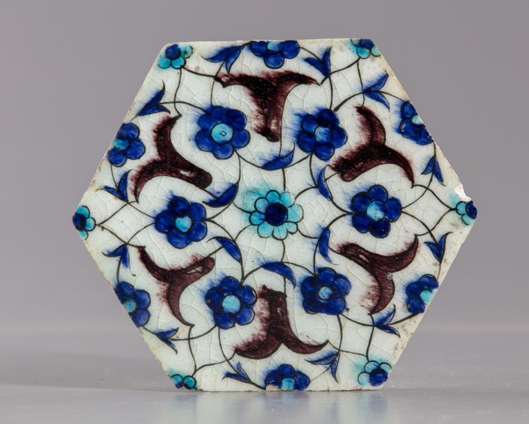 An Ottoman hexagonal Iznik tile An Ottoman hexagonal Iznik tile, decorated in bl…