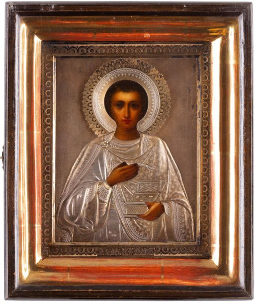 AN ICON SHOWING ST. PANTELEIMON WITH A SILVER GILT OKLAD WITHIN A KYOT Russian, …