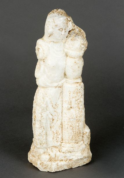 Marble sculpture in ancient manner, of a classical standing figure by a column; …