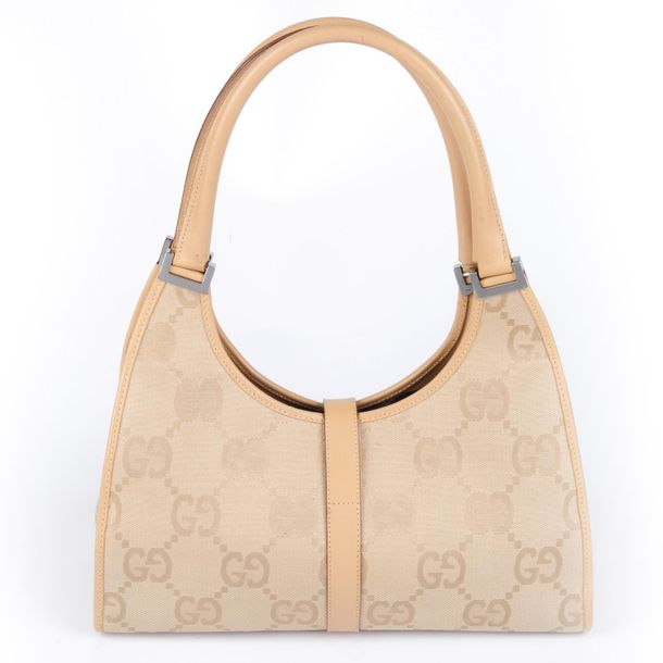 GUCCI a beige Bardot handbag. Designed with the maker's oversized GG canvas exte…