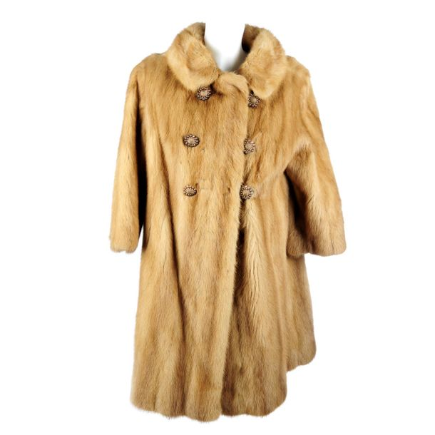 A knee length pastel mink coat. Designed with a notched lapel collar, cropped sl…