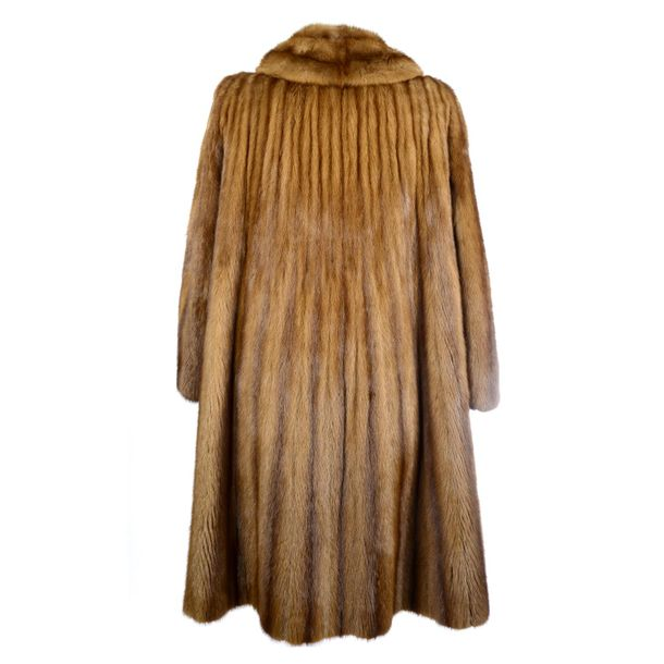 A wild mink coat. Featuring a lapel collar, an open front, two outer pockets and…