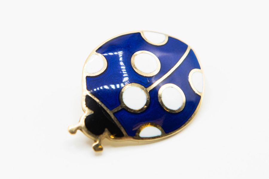 AN 18CT YELLOW GOLD AND ENAMEL BROOCH, formed as a ladybird with blue and black …