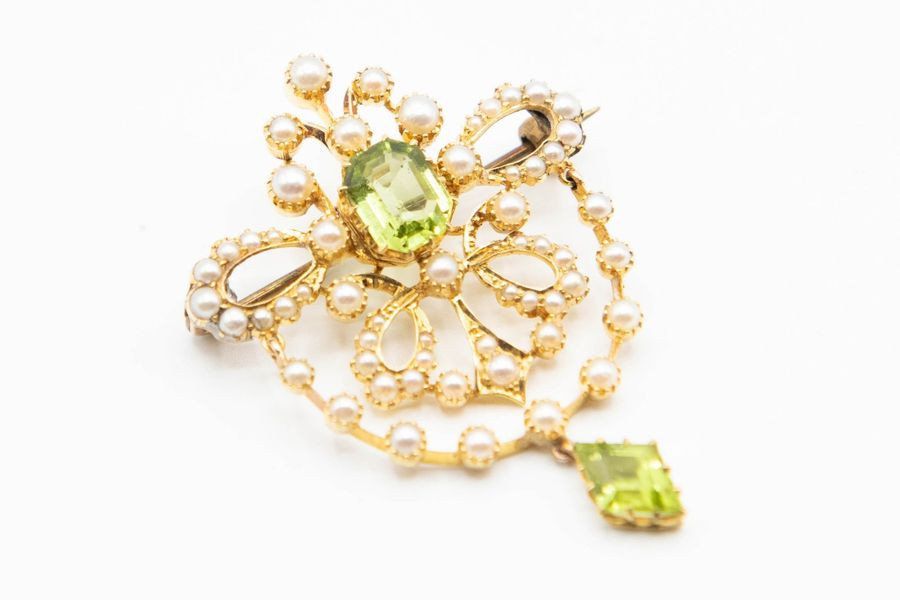 A LATE VICTORIAN SEED PEARL AND PERIDOT BROOCH, the delicate bow detail mount se…