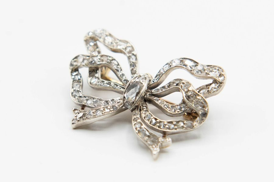 AN EARLY VICTORIAN DIAMOND SET BOW BROOCH, the double ribbon style mount set thr…