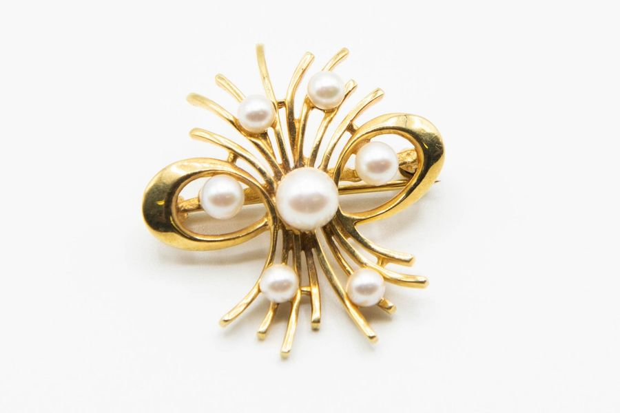A 9CT YELLOW GOLD AND CULTURED PEARL BROOCH, the basket style mount of metal wor…