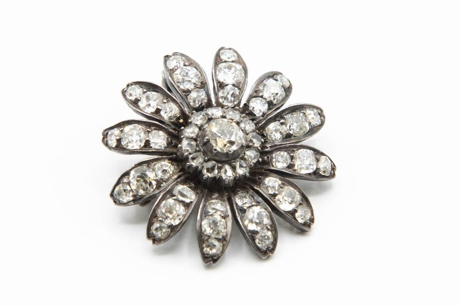 A VICTORIAN DIAMOND SET PENDANT BROOCH, the flower head mount with twelve petals…