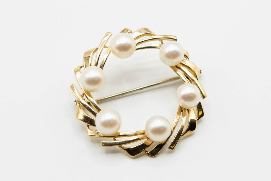 A 14CT YELLOW GOLD AND CULTURED PEARL BROOCH, the wreath design mount set throug…