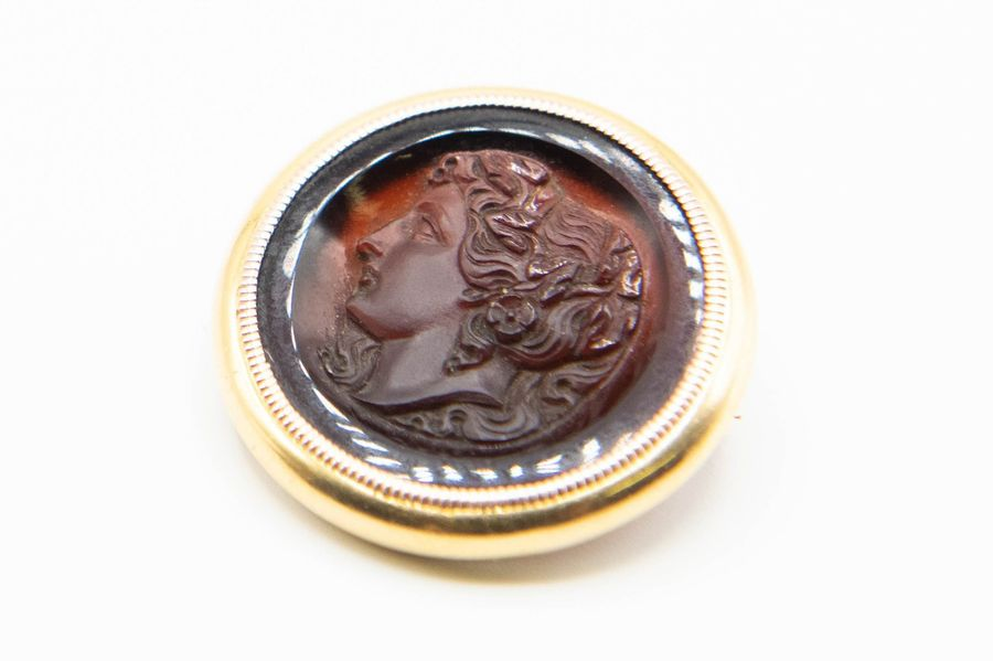 A CARVED CARNELIAN INTAGLIO, the circular carnelian plaque carved to centre with…