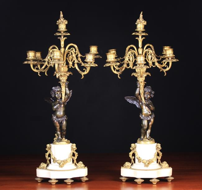 A Pair of 19th Century Louis XVI Style Figural Bronze Candelabra. The winged bac…