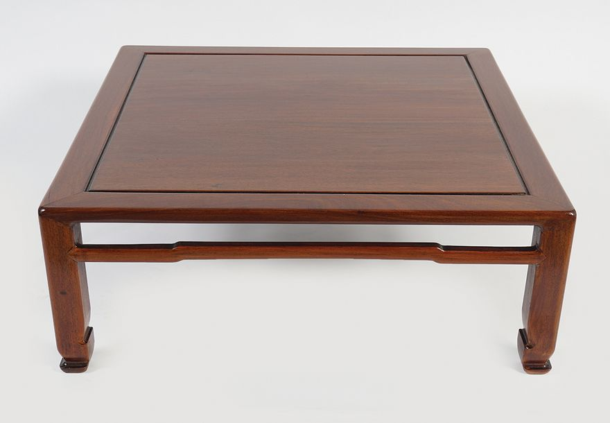 CHINESE QING HARDWOOD KANG TABLE the square panelled top, raised on square scrol…