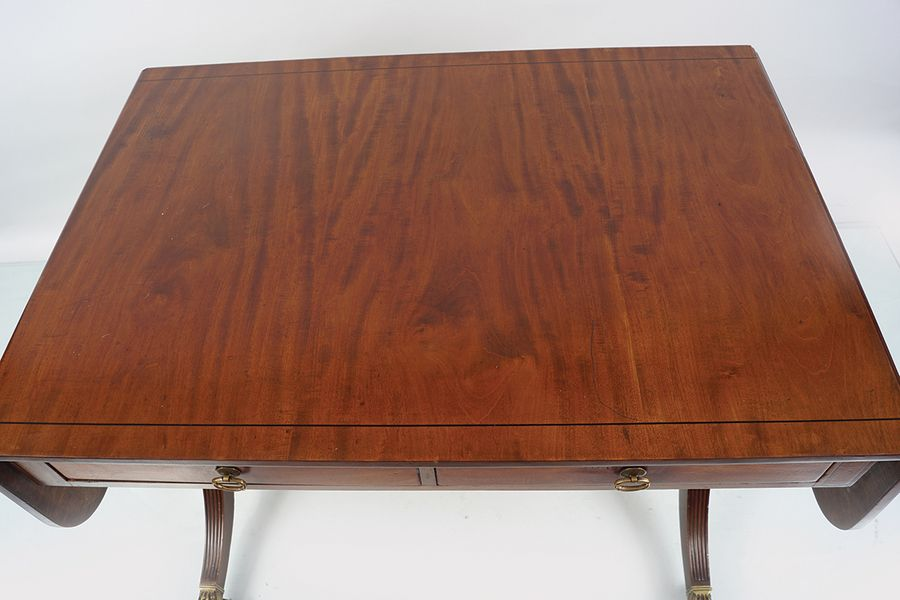 EDWARDIAN MAHOGANY SOFA TABLE Stamped Warring & Gillows, the rectangular top wit…