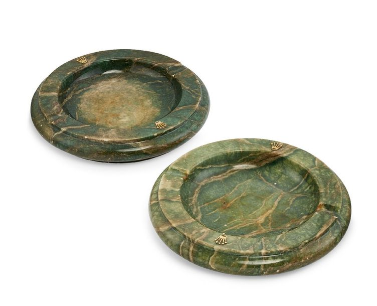 Two marble ash trays by Rolex, each of green stained marble and of circular form…