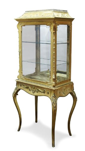 A French gilt metal mounted and silk vitrine, late 19th Century, the shaped corn…