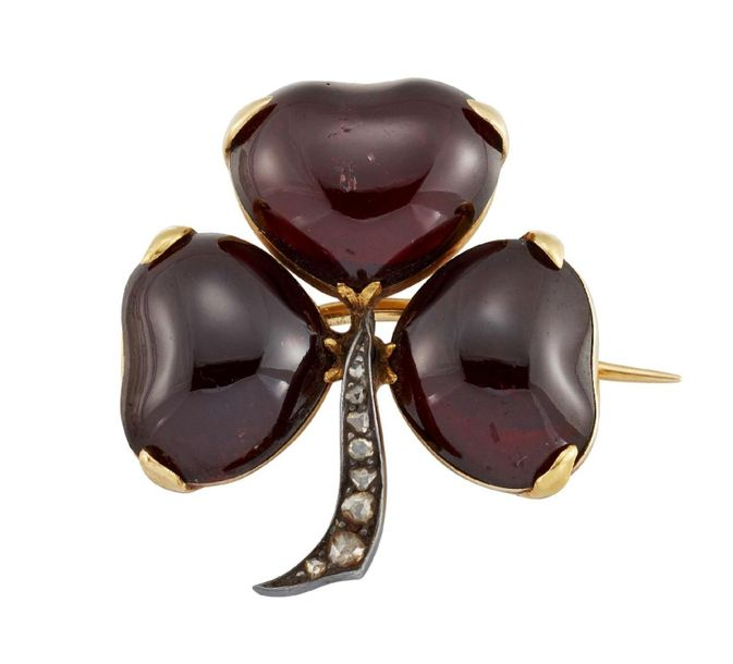 A Victorian garnet and diamond shamrock brooch, each leaf designed as a heart sh…