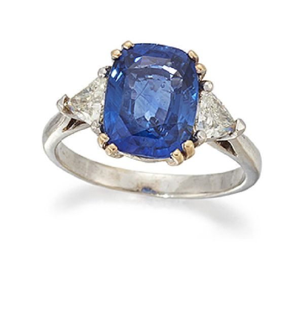 A sapphire and diamond three stone ring, the cushion shaped sapphire centre betw…