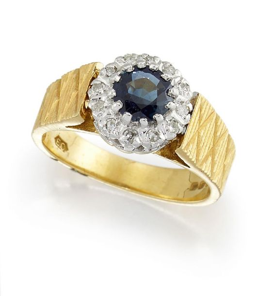 An 18ct gold, sapphire and diamond ring, the circular cut sapphire within a sing…