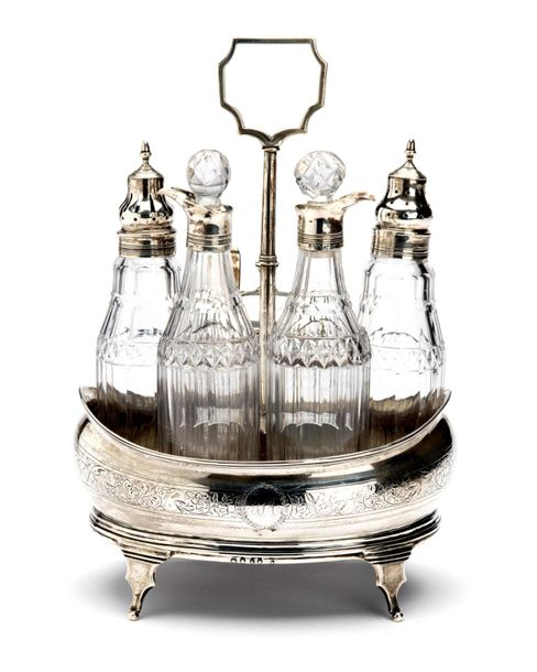 An English silver cruet set with cut glass bottles and silver covers An English …