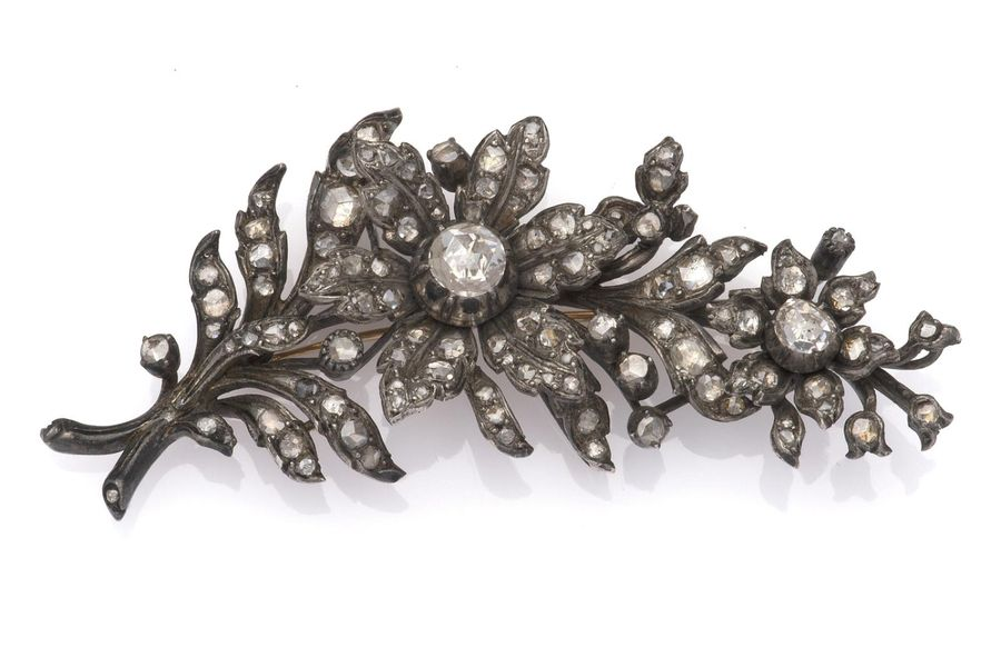 A 14k gold and silver diamond flower brooch A 14k gold and silver diamond flower…
