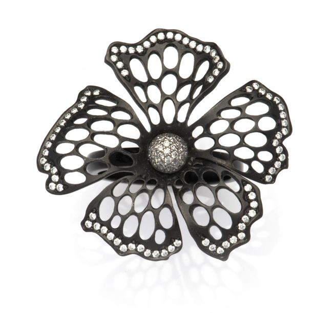 A titanium and diamond flower ring A titanium and diamond flower ring, The front…