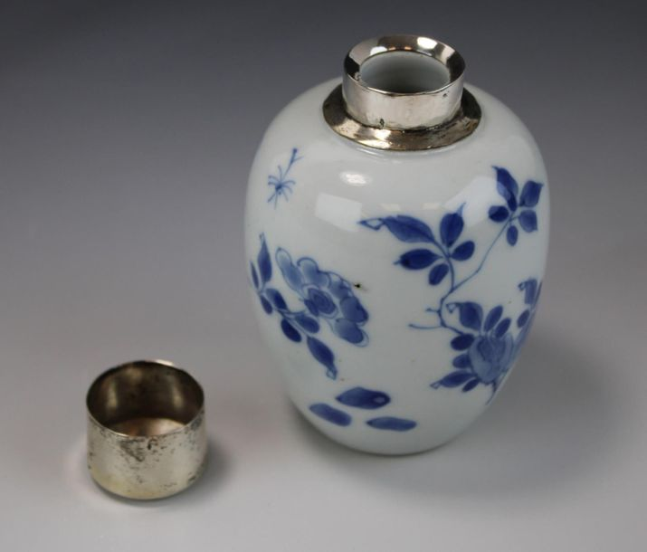 A blue and white tea canister with silver top A blue and white tea canister with…