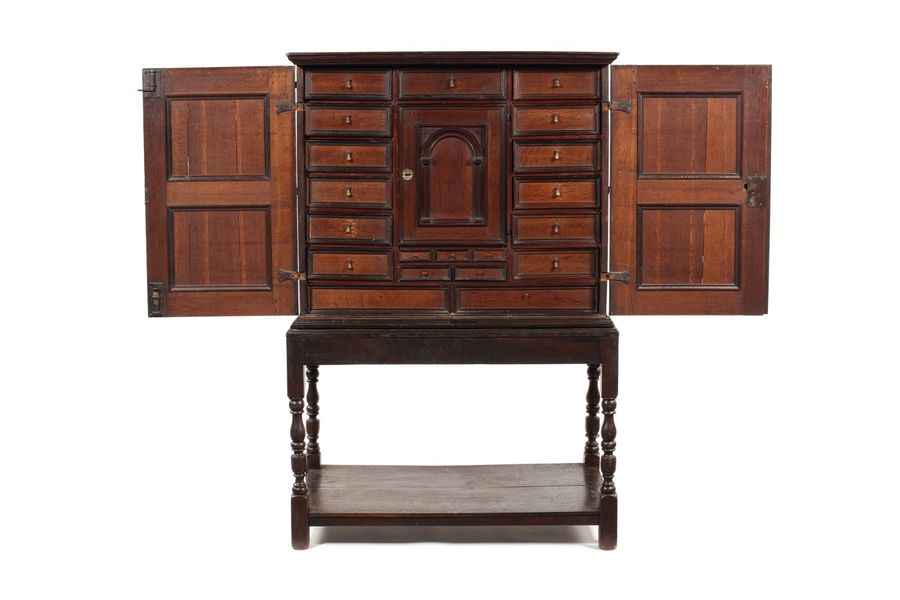 A 17th century Dutch oak and purpleheart cabinet on later stand A Dutch oak and …