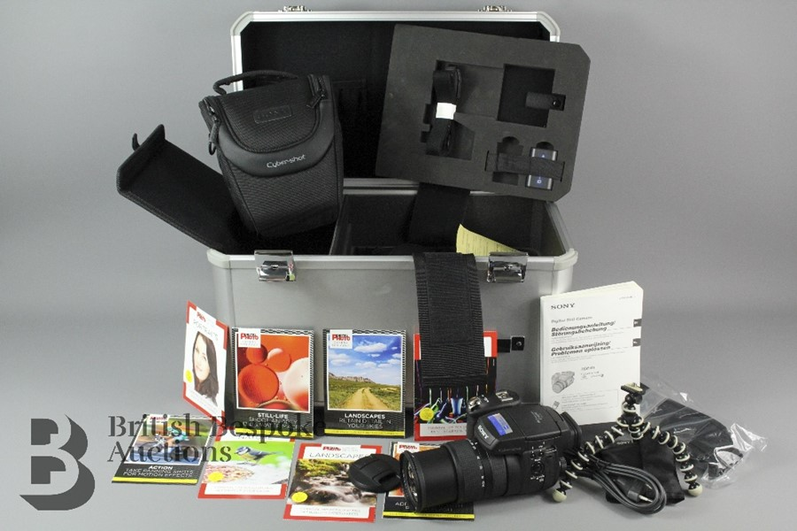 A Sony CyberShot DSC R1 camera with instruction booklets, battery, battery charg…