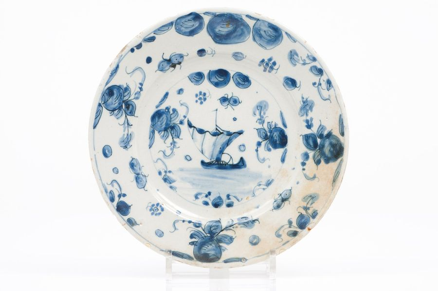 A plate Delft faience  Blue decoration with ship and flower and foliage motifs t…