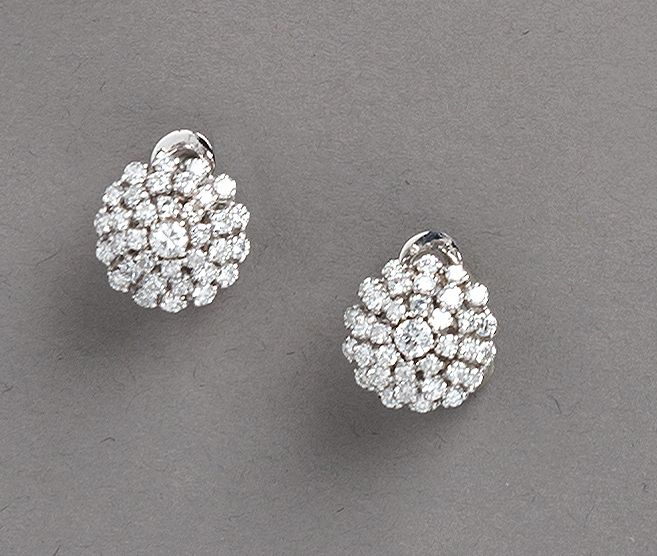 PAIRE DE CLOUS D'OREILLES circulaires en or gris serti de diamants dont un au centre…