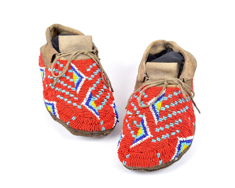 A pair of Plains moccasins hide with red, light and dark blue, white and yellow …