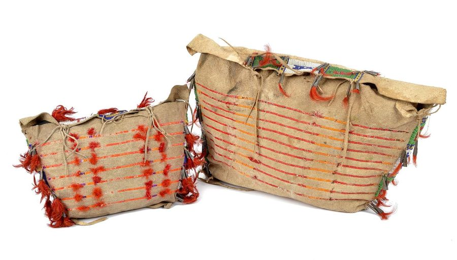 Two Sioux bags Plains hide, stained quill, coloured glass beads, tin cones , fea…