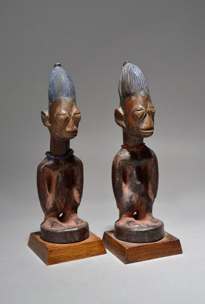 A pair of Yoruba Ibeji male figures Nigeria with bead necklaces, 26cm high, on f…