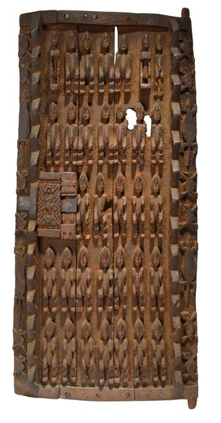 A Dogon door Mali of three boards with relief carved male and female figures, wi…