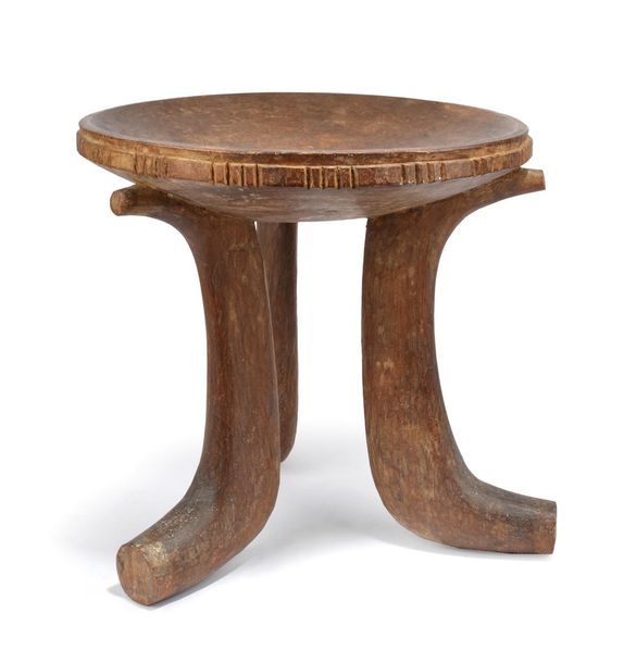 A Jimma stool Ethiopia with a carved edge to the dipped seat and on three scroll…
