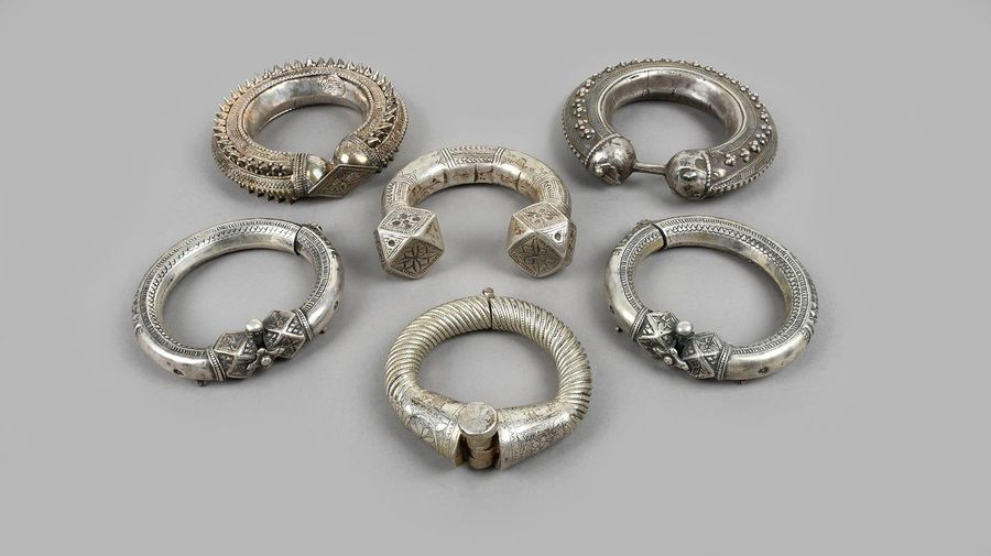 Two Yemen bracelets silver coloured metal with applied florets or cones, one sig…