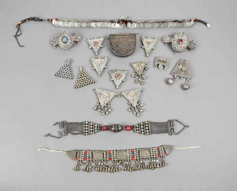 An Egyptian coin head ornament pierced and bound with cotton and silk, with a bu…