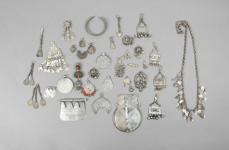 A collection of Nubian pendants silver coloured metal, including two Egyptian te…