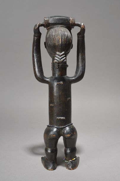 A Baule standing female figure Ivory Coast with a container on her head and wear…