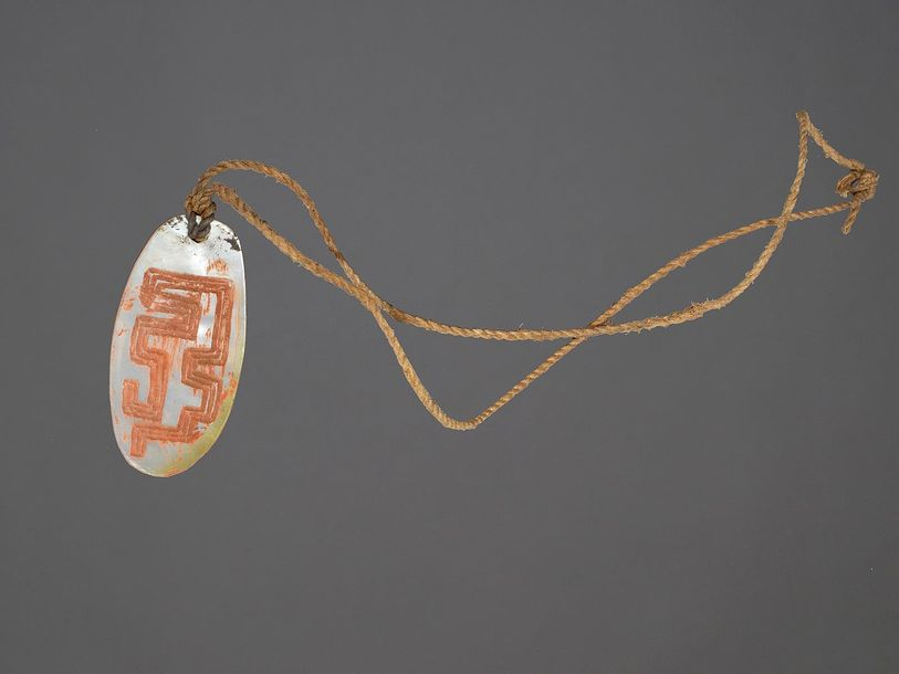 An Aboriginal pendant Kimberly, Western Australia shell with carved linear decor…