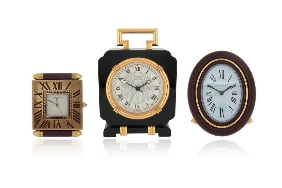 Three travel clocks by Cartier, including a Must de Cartier brass and red enamel…