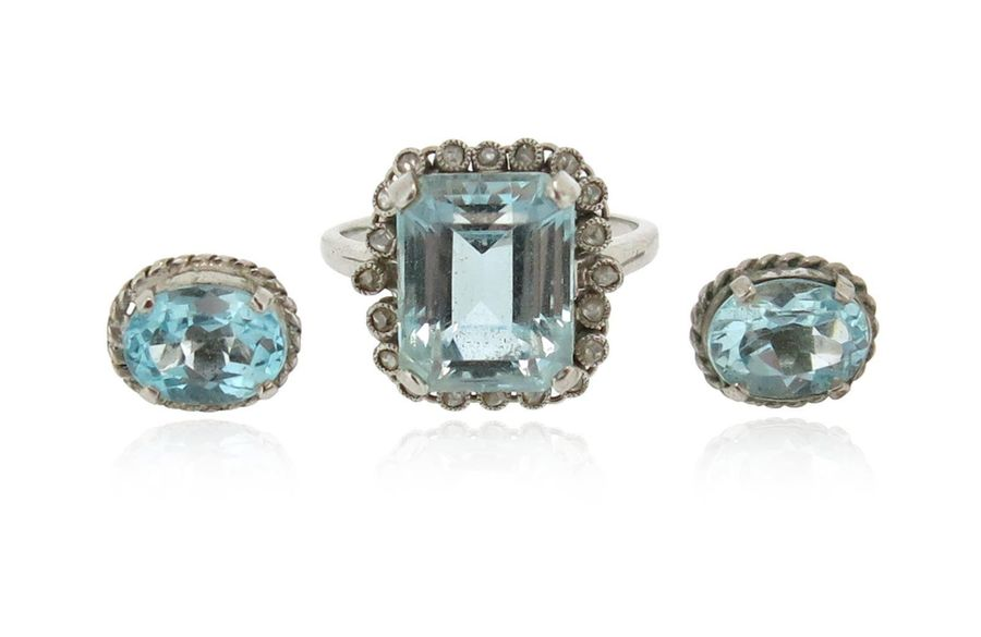 An aquamarine and diamond cluster ring, set with an emerald cut aquamarine withi…