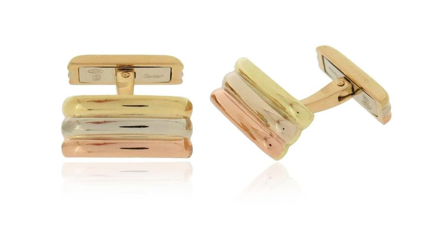 A pair of fluted gold cufflinks by Cartier, in three colour gold, signed and dat…