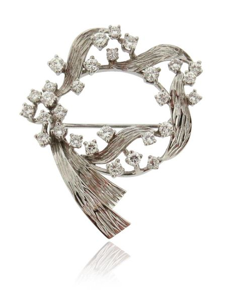 A diamond scroll brooch, set with round brilliant cut diamonds in textured white…