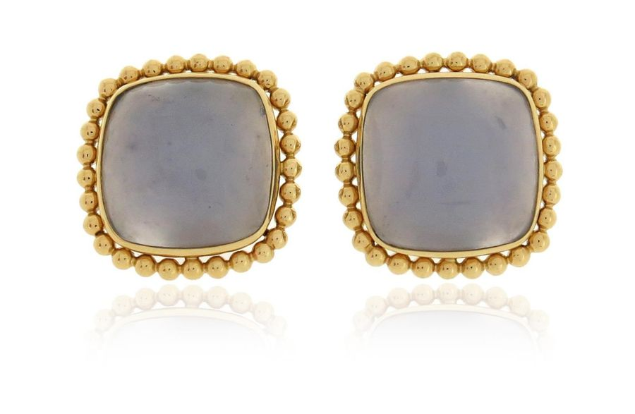 A pair of blue chalcedony cabochon earrings, set within yellow gold pellet borde…