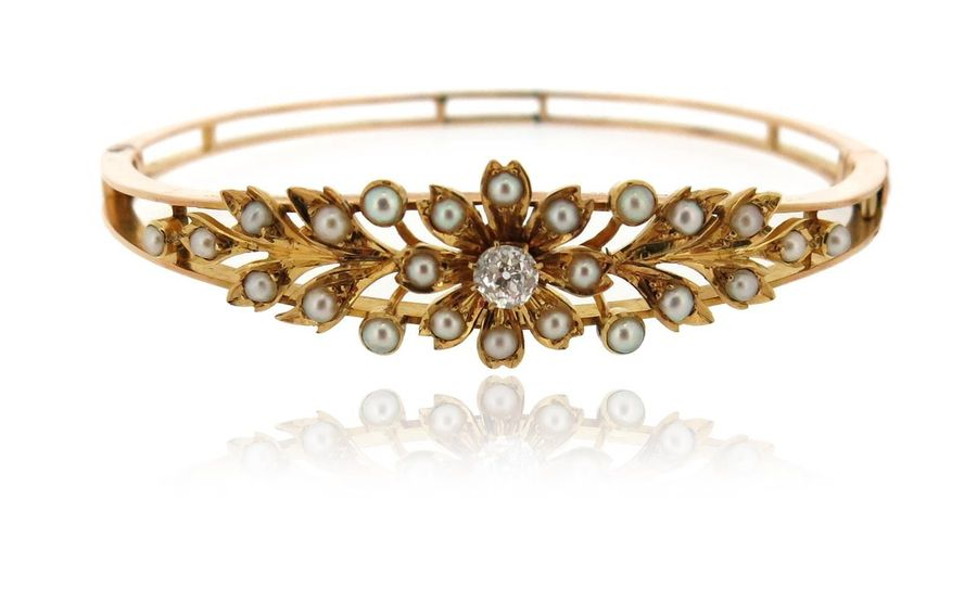 An Edwardian seed pearl and diamond bangle, of laurel design in yellow gold, 5.7…